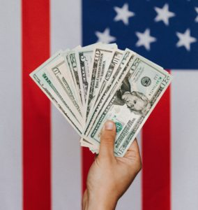 Hand holding cash with American Flag in background